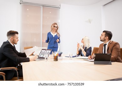 Team of business people at meeting in the conference room. Two successful business women and two businessmen at the desk. They are discussing new projects
