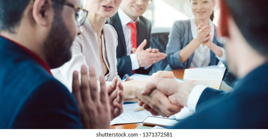 Team of business people negotiating an agreement closing the deal with handshake
