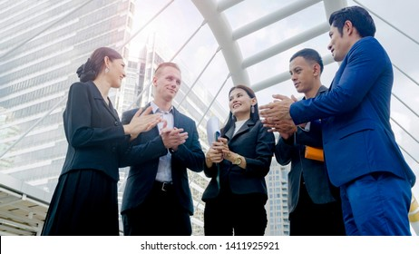 team of business people smart man and woman clap hand for celebrate for colleague staff and manager in good feeling at outdoor pedestrian walk way.