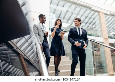 team business people wear suit and walking down on step of stair and holding smartphone and tablet