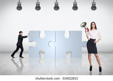 Team of business people working together and try to join puzzle in the grey room.
