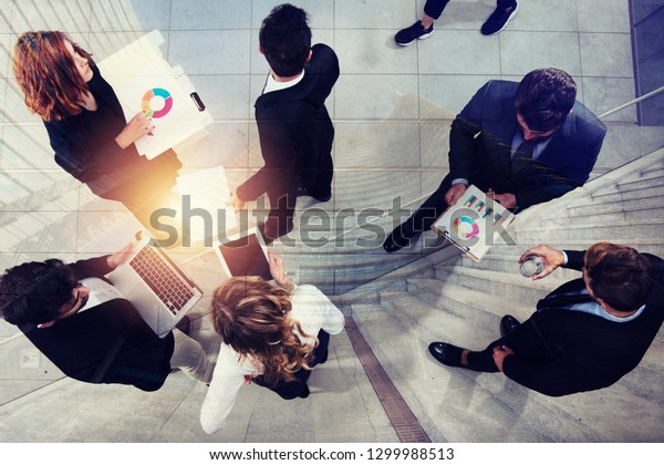 Team of business person works together on company statistics. Shooted from above. Concept of teamwork and partnership