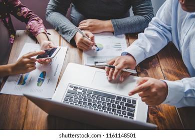 Team businessman job . working with laptop in open space office. Meeting report in progress.