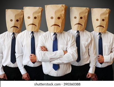 Team of businessman with a paper bag with sad face on the head
