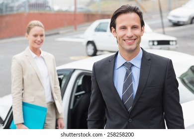 Team of businessman smiling at camera outside the car