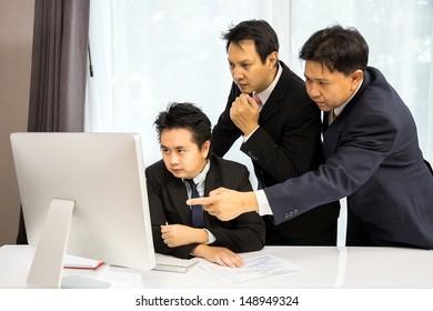 Team of businessmen analysis their business with computer desktop