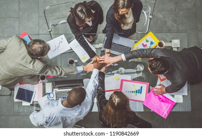 Team of businessmen joining hands during a successful meeting - CEO and managers in a company office, concepts about team work and unity, view from above