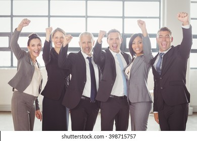 Team of businesspeople cheering with clenched fist in the office