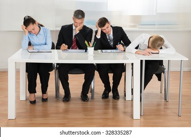 Team Of Businesspeople Getting Bored While Working At Desk In Office