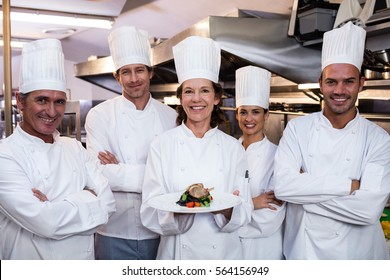Team of chefs in the kitchen with one presenting a dish
