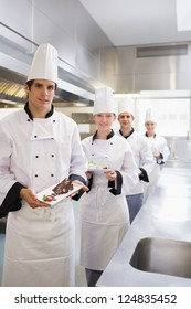 Team of Chef's presenting deserts in the kitchen