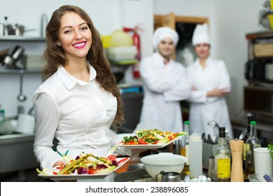 Team of chefs and young beautiful waiter in restaurant kitchen
