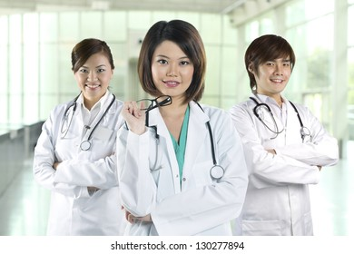 Team of Chinese doctor's wearing a white coat and stethoscope. Three Asian doctors wearing lab white coats standing in a hospital.