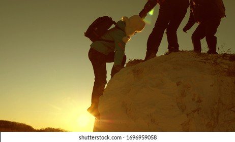 team of climbers climbs a mountain holding out helping hand to each other. Free woman traveler climb mountain. teamwork of tourists. Travel and adventure in mountains at sunset.