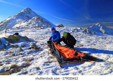Team of climbers on snowy mountain prepares the camp for the night