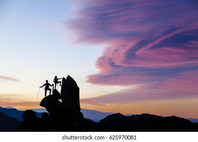 Team of climbers on the summit as the sun sets.