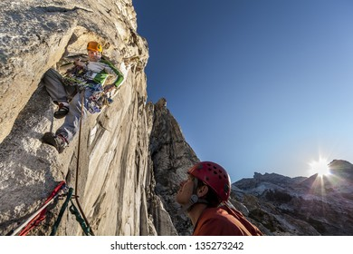 Team of climbers struggle up a steep and challenging rock spire.