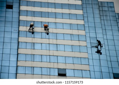 Team of climbing workers clean the windows on a glass facade of a skyscraper