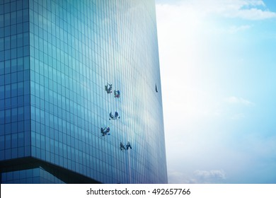 A Team Of Climbing Workers Clean the Windows on Skyscraper