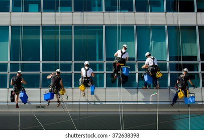 Team Of Climbing Workers Cleaning an Office Building