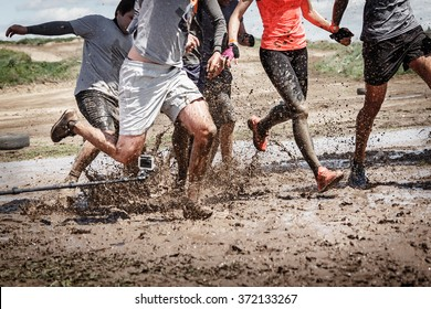 Team competition with an obstacle. Finish team in a big mud puddle. Close-up