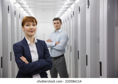 Team of computer technicians looking at camera in large data center