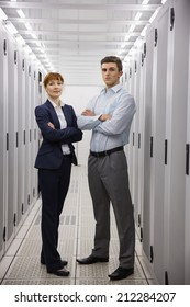 Team of computer technicians smiling at camera in large data center