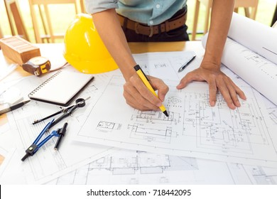 Team of construction engineer working hard project blueprint to build large commercial buildings and golf course houses.