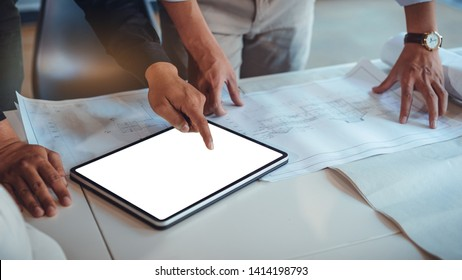 Team of construction engineers discussing paper blueprint and mockup tablet white screen for graphic montage. Architect using technology concept
