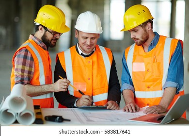 Team of construction workers wearing protective helmets and vests discussing project details with executive supervisor standing at table with blueprints, tools and laptop on it