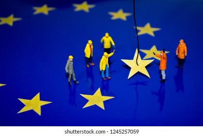 A team of construction workers work to remove a yellow star from the EU flag, representing Brexit.