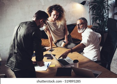 Team of coworkers making great work discussion in modern office.Young business teamwork concept.Bearded man talking with creative director and account manager.Horizontal, blurred background