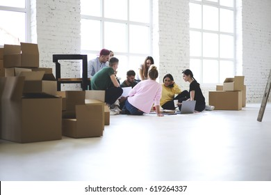 Team of coworkers working together on startup project just moved in new office sitting near carton boxes with stuff and goods, male and female crew members planning how to arrange space with furniture