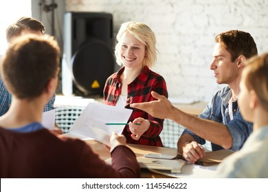Team of creative business professionals discussing ideas while collaborating on startup project during meeting in modern office, focus on blonde young woman smiling cheerfully enjoying work