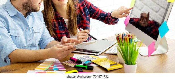 Team of creative designers working on a common project in a design studio