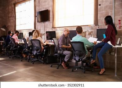 Team Of Designers Working At Desks In Modern Office