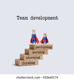 Team development stages. Teamwork concept image with superhero characters on top of the wooden staircase. Words: physiological, safety, love belonging, esteem, self-actualization.  White background.