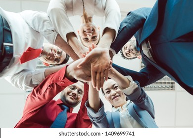 Team of diverse business people stacking their hands together, seen from below