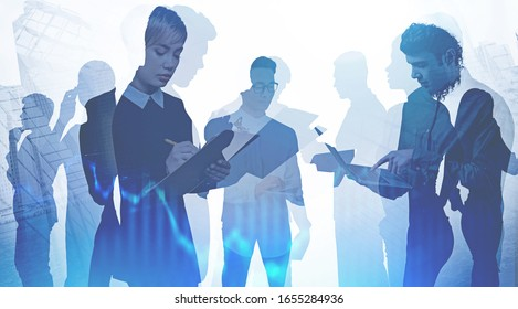 Team of diverse business people working together with gadgets and papers in city with double exposure of blurry graph. Concept of stock market and teamwork. Toned image