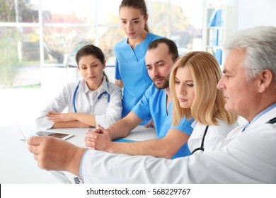Team of doctors exploring roentgenogram at meeting