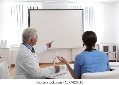 Team of doctors looking at projection screen indoors.