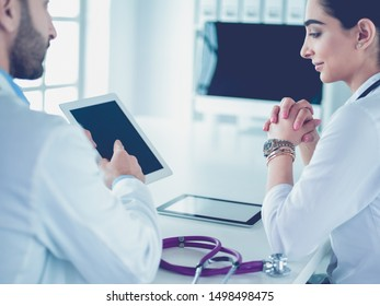 Team of doctors sitting at table in clinic