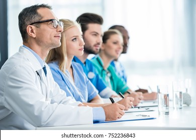 team of doctors sitting at table in row and writing