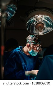 Team of doctors, surgeons and assistants performing difficult surgery in operating theatre