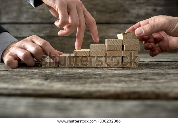 Team effort on the way to success - two male hands building stable steps with wooden pegs for the third one to walk his fingers up towards personal and career growth.