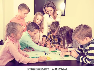 Team of elementary age children and female teacher drawing on one sheet