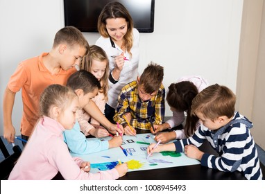Team of elementary age children and young teacher drawing on one sheet