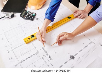 Team of engineer and architect measuring and discussing every detail of construction plan, view from above