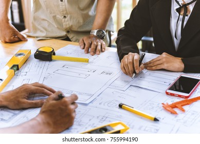 Team engineer asian colleagues discussing and checks construction blueprints on new project at desk in office.