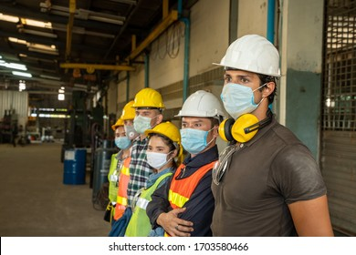 Team engineers and technician wearing protective mask to Protect Against Covid-19 standing at factory.
